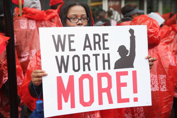 """protestor holding sign that says """"we are worth more"""""""