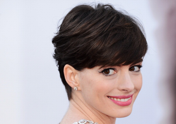 Actress Anne Hathaway smiles while looking over shoulder on the red carpet