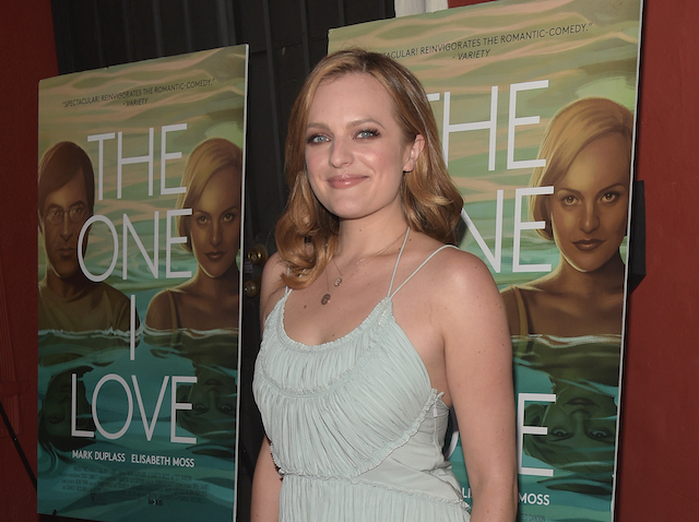 Elisabeth Moss standing in front of a movie poster in a blue dress.