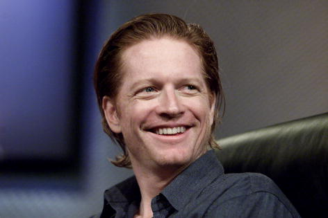 Actor Eric Stoltz smiles while sitting in a black chair