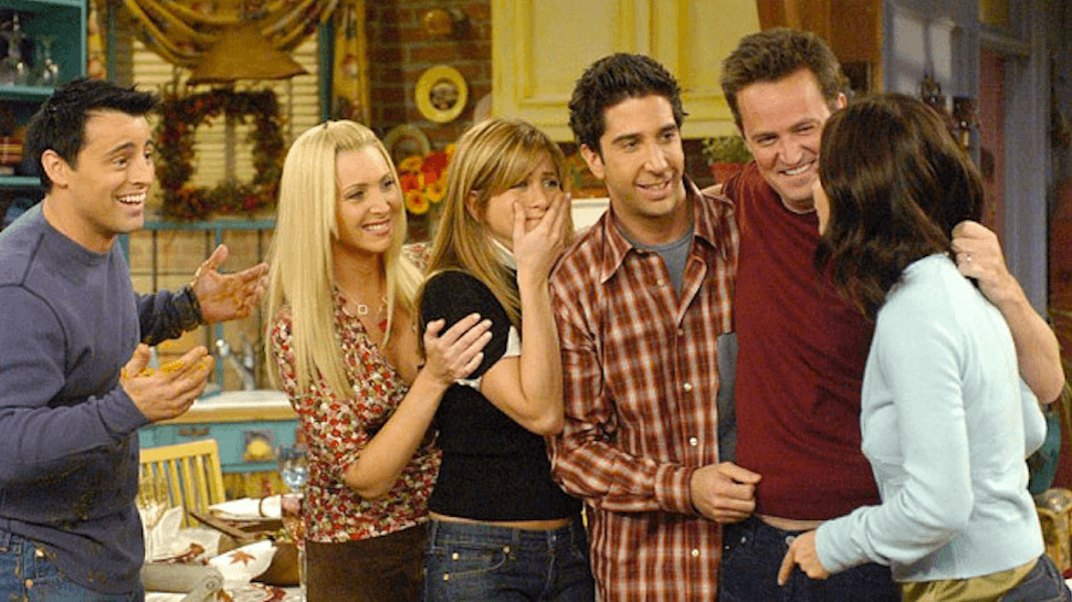 The cast of Friends stand in a line and hug