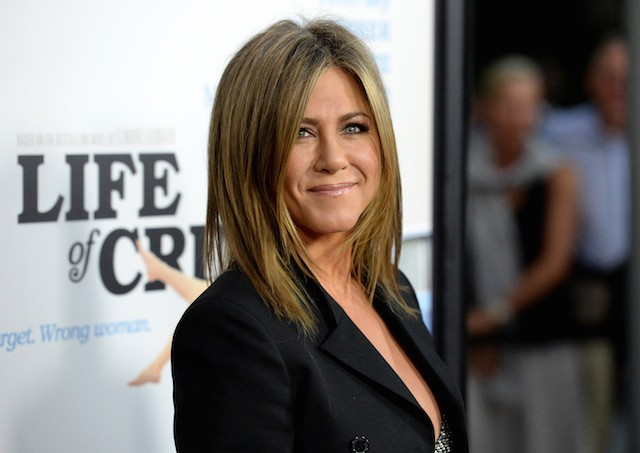 Jennifer Aniston stands in a black blazer smiling to the side as she poses for photos.
