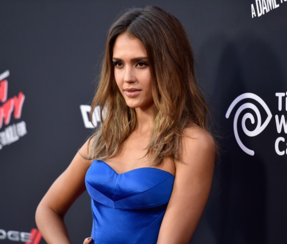 Jessica Alba is in a blue dress on the red carpet with her hand on her hip.