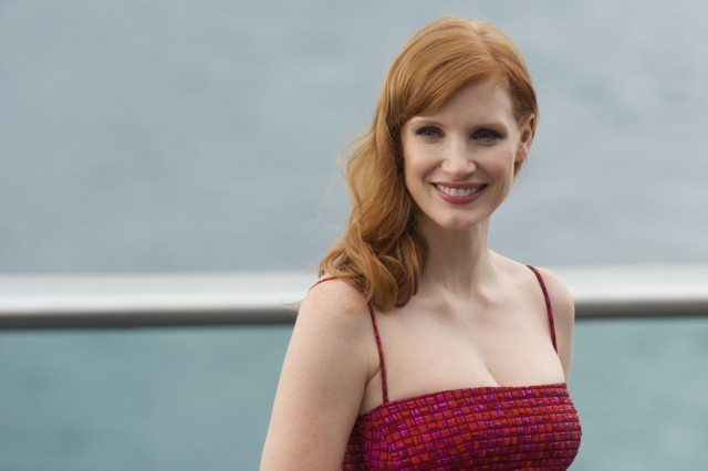 Jessica Chastain smiles and poses for photos while wearing a red dress.