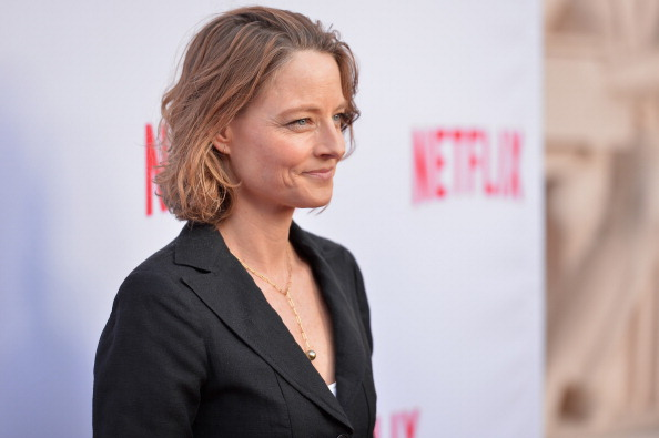 Jodie Foster standing in a black blazer and smiling slightly as she stares straight ahead.