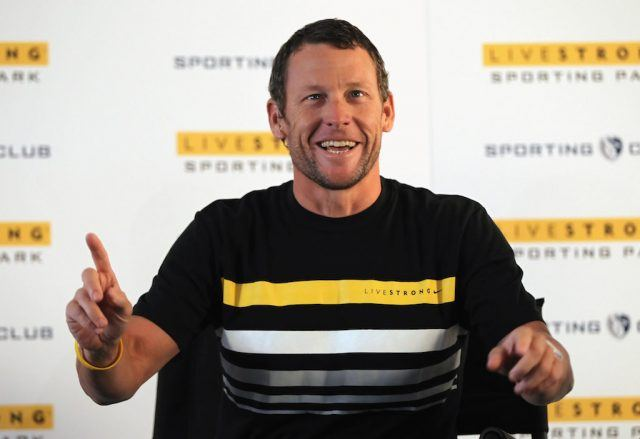 Lance Armstrong sitting and speaking as she gestures with a finger.