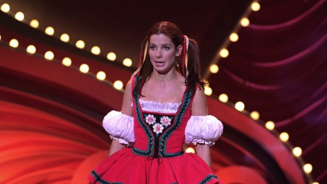 Sandra Bullock stands on stage in a costume