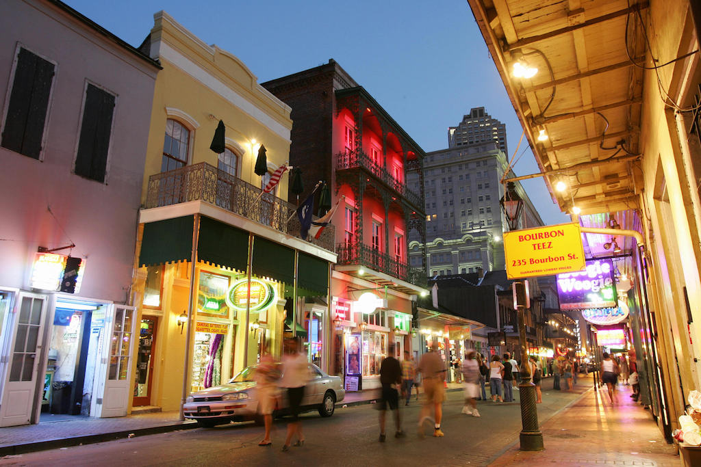 Dusk falls over Bourbon Street in the French Quarter of New Orleans, 11 July 2006, almost one year after Hurricane Katrina devastated the city. For tourists strolling through the French Quarter it's easy to forget that Hurricane Katrina ravaged New Orleans a year ago. The beignets are fresh, trinkets and designer clothes are artfully arranged in shop windows, and hurricanes are spinning in the bars on Bourbon Street. But while the music, food and good times have come back, the crowds have not and the city is struggling to make ends meet while its main industry remains crippled. With more than 10 million visitors a year, tourism was once a 5.5 billion dollar industry in New Orleans, accounting for 40 percent of the city's tax revenues and employing 85,000 people. (Photo by Robyn Beck/AFP/Getty Images)
