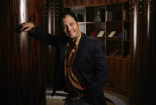 Rob Schneider is smiling and leaning against a wall.