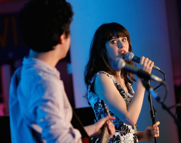 Zooey Deschanel singing into a microphone on stage as she looks over to a guitarist.