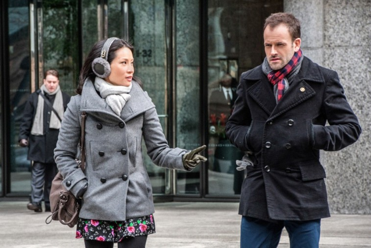 Jonny Lee Miller and Lucy Liu converse on the street in a scene from Elementary
