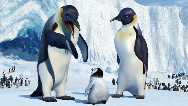 Three animated penguins stand together in a scene from Happy Feet