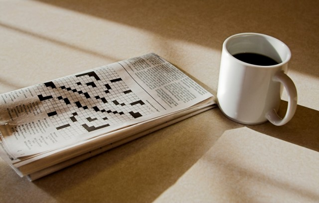 a cup of coffee and a crossword puzzle