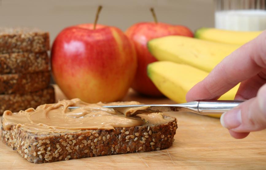Person spreading peanut butter on a slice of bread