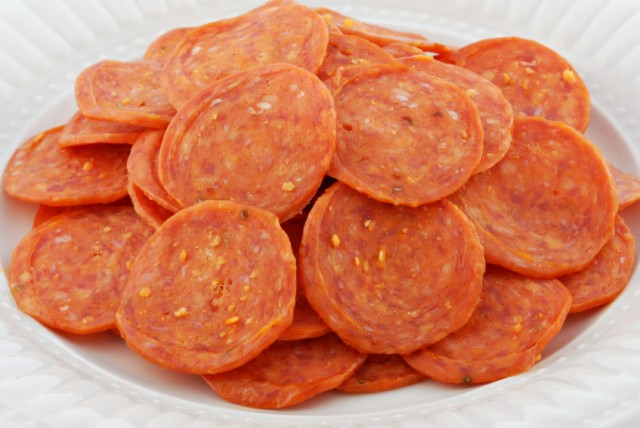 Pepperonis on a white plate.