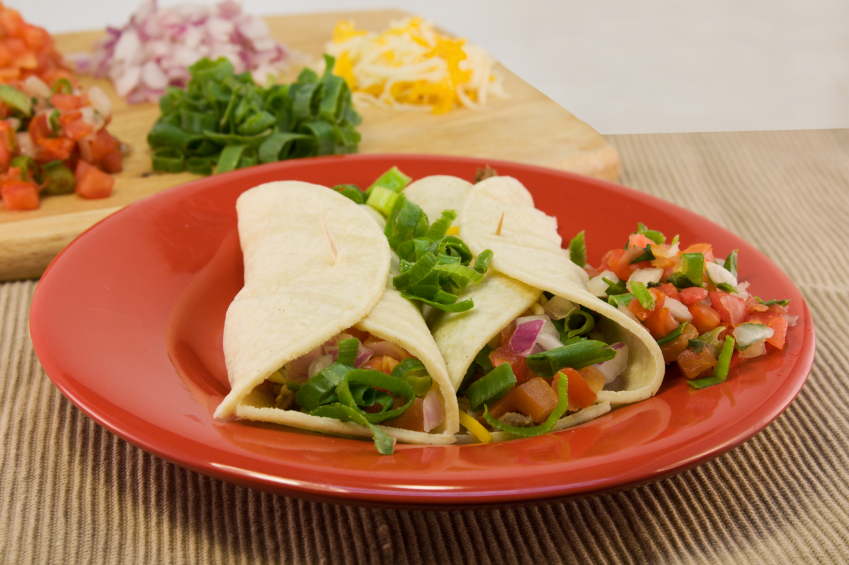 Soft tacos with salsa on a red plate