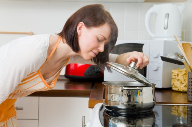 woman smelling her dish while it's cooking