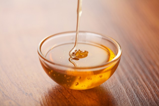 honey being poured into a small bowl