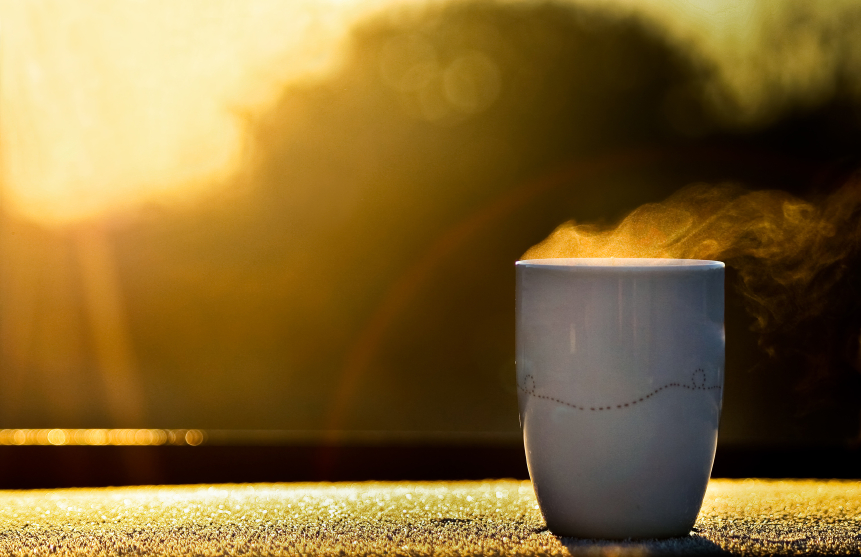 steaming mug of coffee in front of a window
