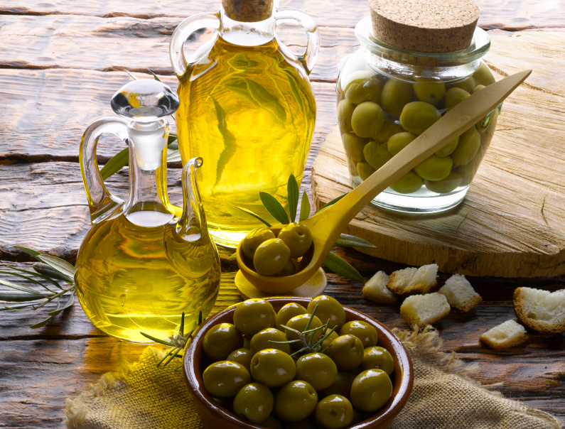 olives next to olive oil on a table