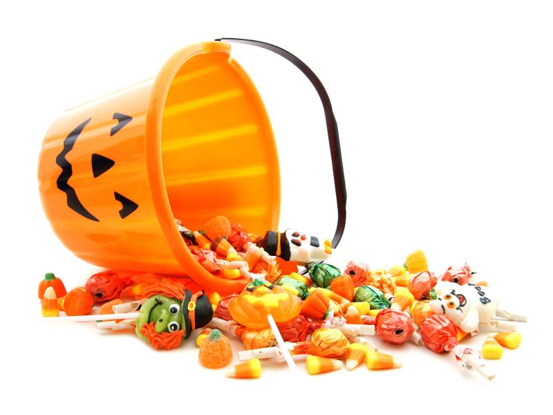 Halloween candy spilling from a pumpkin bucket