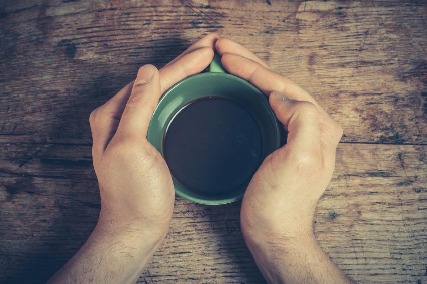 man cupping a mug of coffee