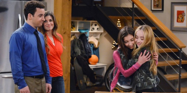 Corey and Topanga smile as two young girls embrace in a hug.