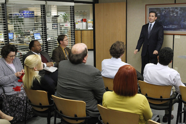 Steve Carell stands in front of a packed conference room in The Office