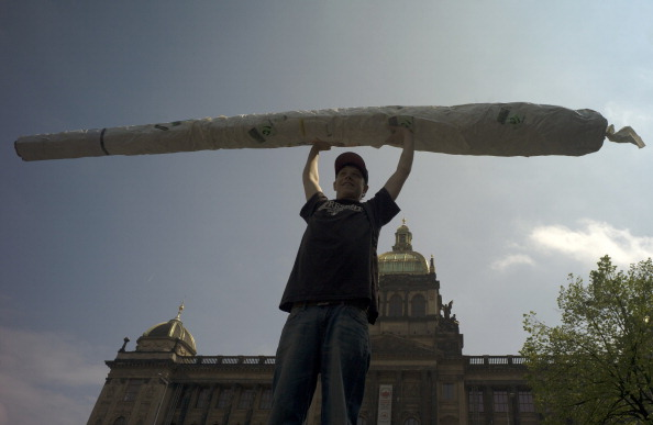 A protester holds up a imitation of a big joint as he takes part in a demonstration for the legalization of marijuana, in Prague on May 4, 2013. (Photo source: Michal Cizek/Getty Images)
