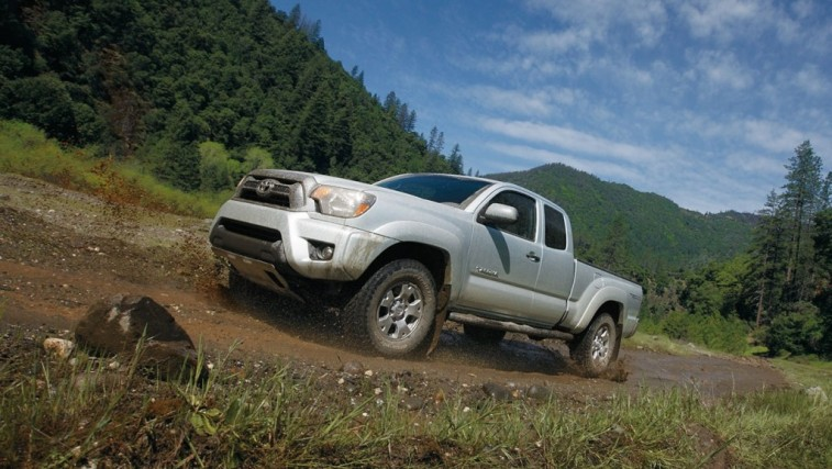 A 2015 Toyota Tacoma driving across a muddy road