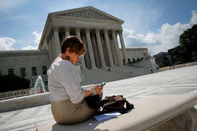 Kirsten Luna from Holland, Michigan, uses her smartphone outside the U.S. Supreme Court after a major ruling on cell phone privacy by the court June 25, 2014