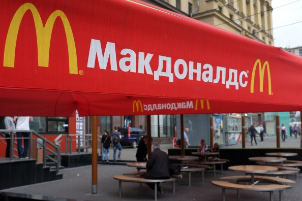 People sit on the terrace of a closed McDonald's restaurant, the first to be opened in the Soviet Union in 1990, in Moscow on August 21, 2014. Russian authorities shuttered four Moscow McDonald's due to alleged sanitary violations on August 20, 2014, including a restaurant that once symbolised reviving Soviet-US ties, as tensions sizzled over Ukraine.  The announcement comes in the wake of Russian bans on US and EU food imports in response to Western sanctions over Moscow's perceived backing for rebels in eastern Ukraine. (Photo by Alexander Nemenov/AFP/Getty Images)