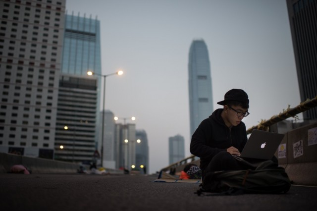 A pro-democracy protester using a laptop computer as he sits on an occupied road in the Admiralty district of Hong Kong early on October 8, 2014