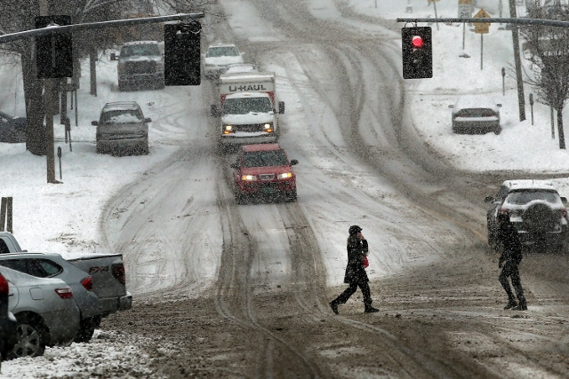 BURLINGTON, VT - FEBRUARY 05: Pedestrians and cars contend with heavy snow on February 5, 2014 in Burlington, Vermont. Burlington, and much of the Northeast, received another mix of wintery weather on Wednesday causing traffic accidents and hundreds of flight cancelations. (Photo by Spencer Platt/Getty Images)