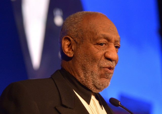 Bill Cosby is speaking at a microphone.