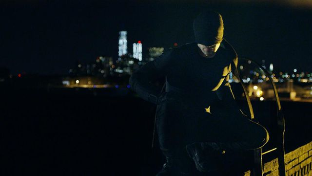Charlie Cox in a black costume on a city roof in 'Daredevil.'