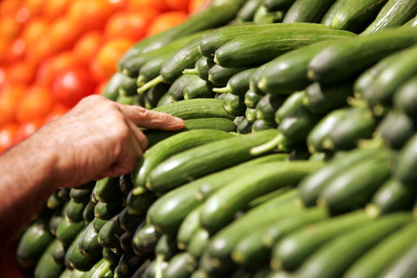 A person looks at green zucchinis at a supermarket grocery section.