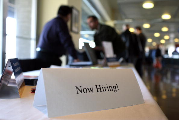 """SAN FRANCISCO - MARCH 19:  A """"now hiring"""" sign is posted on a table during the Recruit Military Career Fair March 19, 2009 at AT&T Park in San Francisco, California. Hundreds of military veterans attended the career fair that was open only to veterans.  (Photo by Justin Sullivan/Getty Images)"""