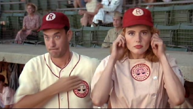 Tom Hanks holds his hand over his heart while wearing a baseball uniform and standing next to Geena Davis in A League of Their Own