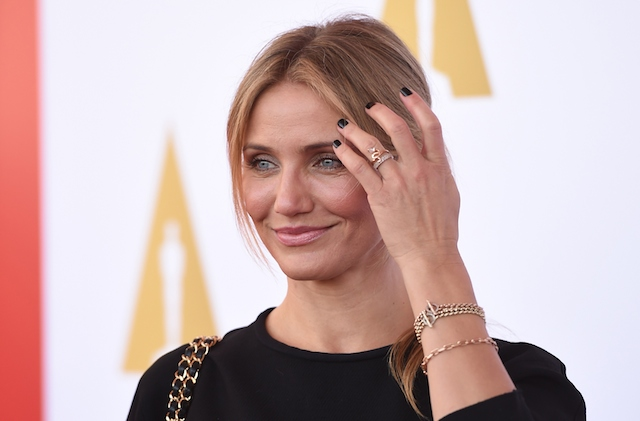 Cameron Diaz brushes away her hair while smiling on a red carpet.
