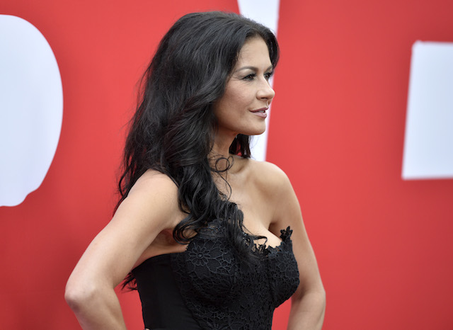 Catherine Zeta-Jones poses on a red carpet with her hands on her hips.