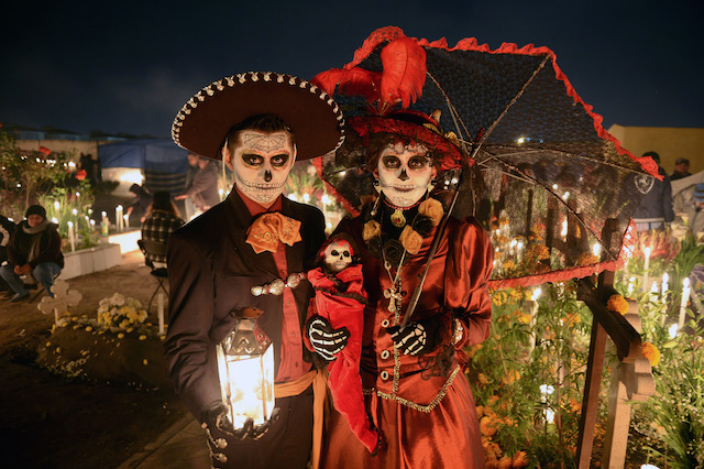Two people celebrating Day of the Dead in a cemetery.