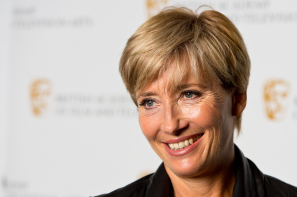 Emma Thompson smiling in a black shirt at a movie premiere.