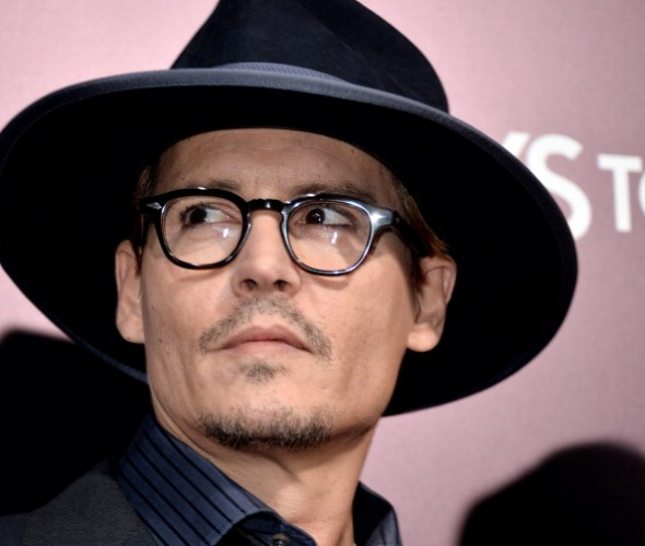 Johnny Depp looking upwards while wearing glasses and a black hat.