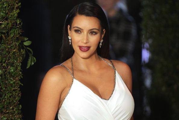 Kim Kardashian poses in a white dress.