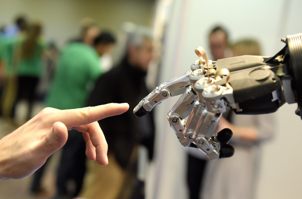 """A man moves his finger toward SVH (Servo Electric 5 Finger Gripping Hand) automated hand made by Schunk during the 2014 IEEE-RAS International Conference on Humanoid Robots in Madrid on November 19, 2014. The conference theme """"Humans and Robots Face-to-Face"""" confirms the growing interest in the field of human-humanoid interaction and cooperation, especially during daily life activities in real environments. Photo by Gerard Julien/AFP/Getty Images."""