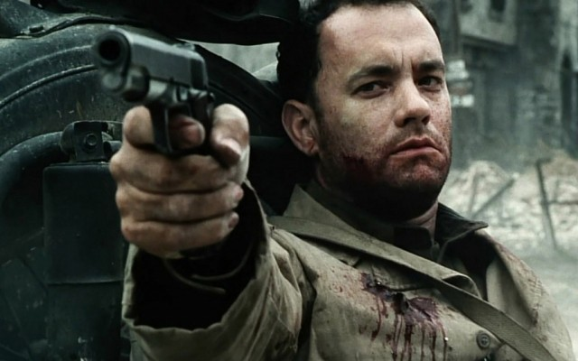 Tom Hanks holds up a gun while wearing a bloodied jacket in Saving Private Ryan