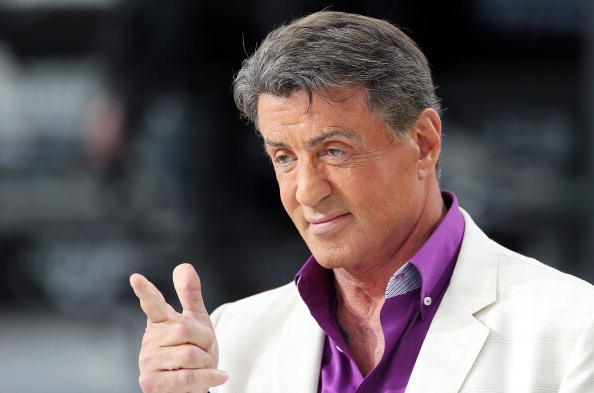 Sylvester Stallone is smiling and pointing.