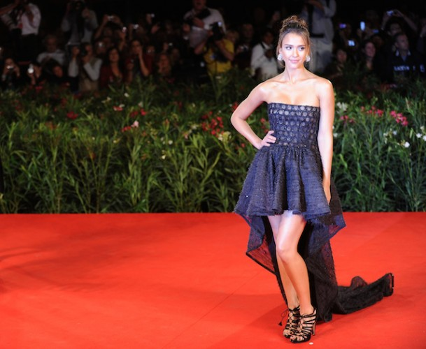 Jessica Alba poses with her hand on her hip while standing on a red carpet.