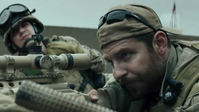 Bradley Cooper adjusts a sniper rifle in a scene from American Sniper